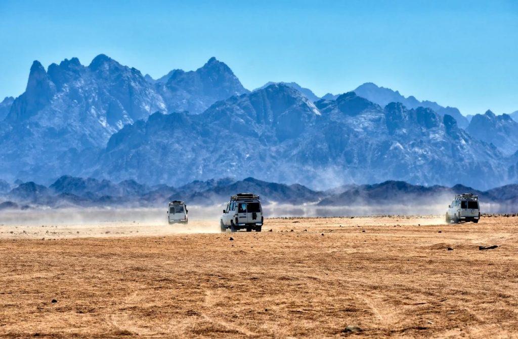 Drei Jeeps fahren durch die aegyptische Wueste