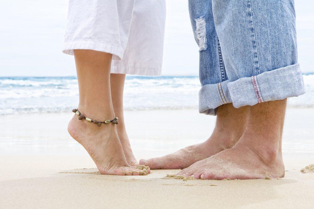 Füße und Unterschenkel von Frau und Mann an einem Strand Sie steht auf Zehenspitzen und ist ihm zugewendet