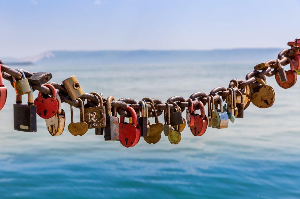 Liebesschlösser an Geländer befestigt mit Gewässer im Hintergrund
