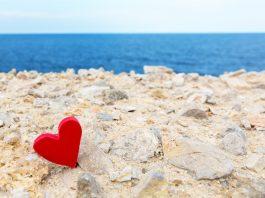 Rotes Herz liegt im Sand vor Meerpanorama