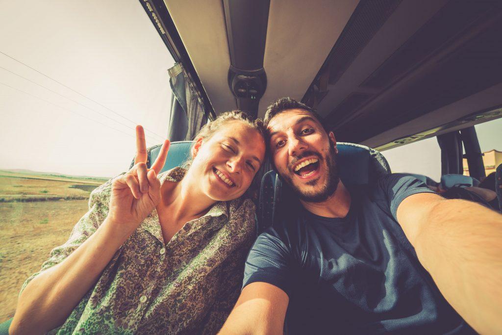 Reisendes Paar sitzt in einem Bus und lacht in die Kamera