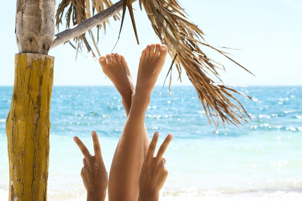 Frau im Urlaub liegt in Haengematte am Strand