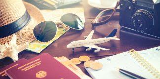 Reisepass un Reiseutensilien sidn auf einem Tisch ausgebreitet