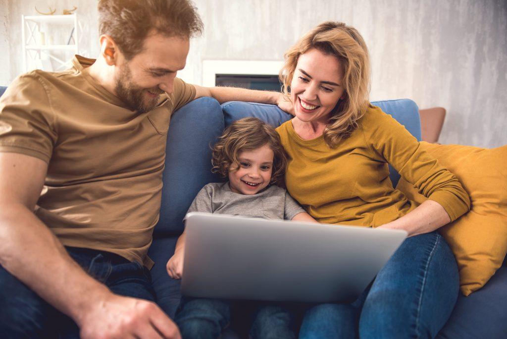 Eltern und Kind sitzen vor einem Laptop und buchen online eine Reise