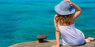 Frau sitzt mit Sonnenhut auf einem Felsen am Wasser