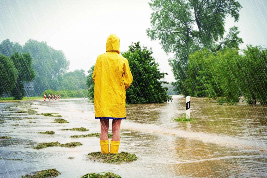 Person steht im gelebn Regenmantel im Regen