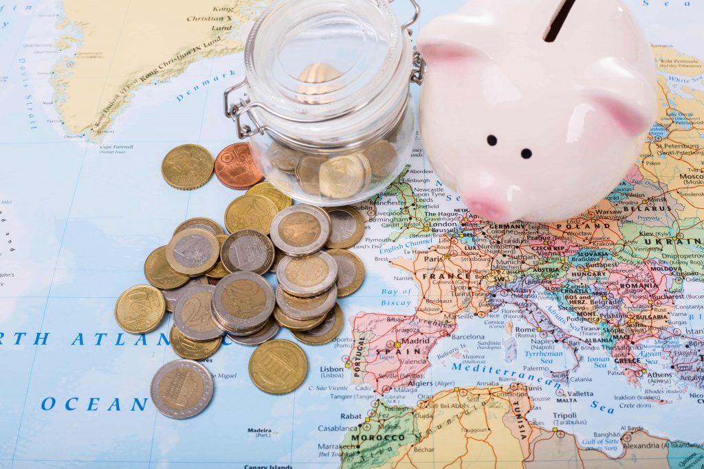 Sparschwein Reisebudget liegen auf Weltkarte