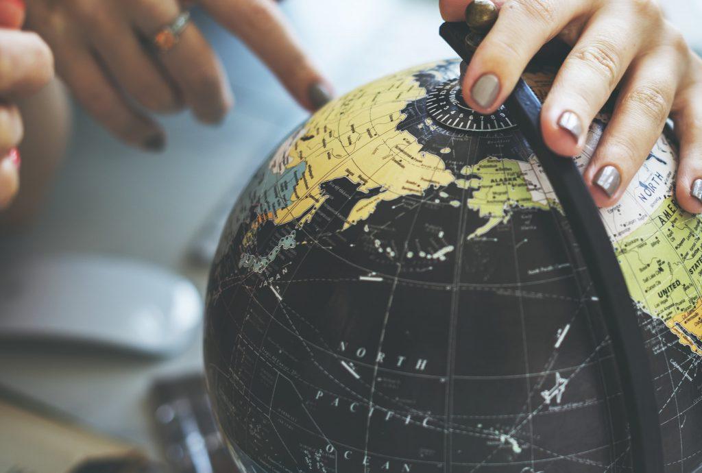 Finger zeigt auf Reiseziel auf einem Globus