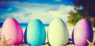 Ostereier stehen nebeneinander an einem Strand