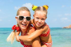 Mutter trägt Tochter Huckepack am Meer