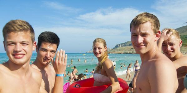 Vijf tieners op het strand.