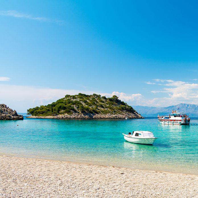 Mooi eiland in helderblauwe zee met twee boten ervoor.