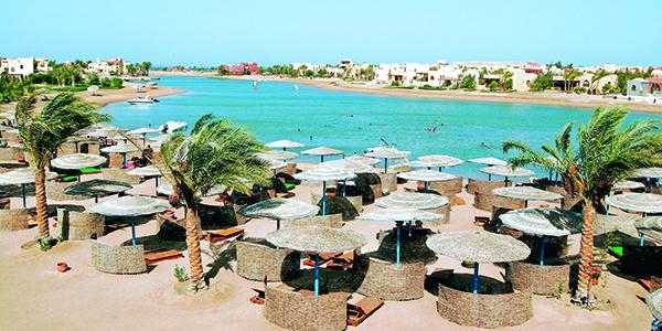 Uitzicht op helderblauwe lagune en ligbedjes met rieten parasolletjes bij The Three Corners Rihana Resort & Inn in Egypte