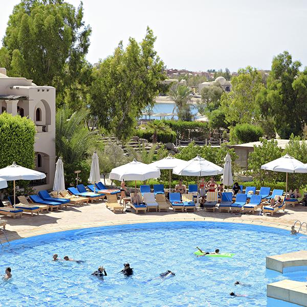 Uitzicht op zwembad en groene tuin van The Three Corners Rihana