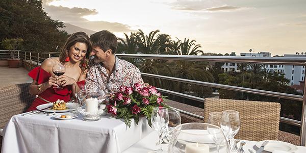 Chic aangekleed koppel geniet van romantisch diner met mooi uitzicht.