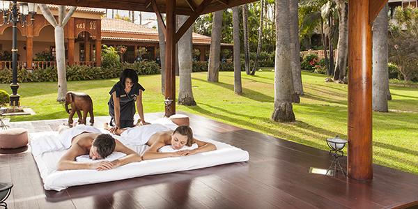 Koppel krijgt massage in de buitenlucht in luxe spa.