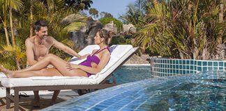 Koppel op luxe ligbedden aan zwembad