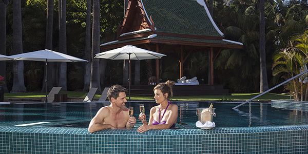 Koppel drinkt een glaasje champagne aan de rand van het zwembad.