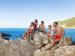 Groot gezin op een rots tijdens de zomervakantie