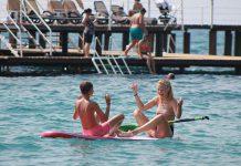 Twee kinderen hebben plezier op stand up paddling board