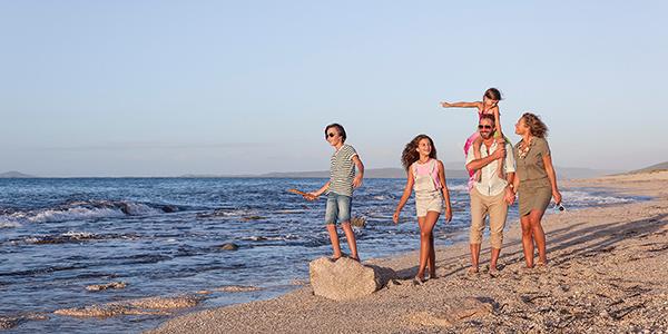 Ouders met drie kinderen lopen vrolijk over het strand.