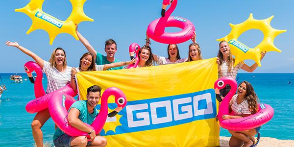 Groep jongeren poseert vrolijk met GOGO vlag en opblaasbare zon en flamingo's.
