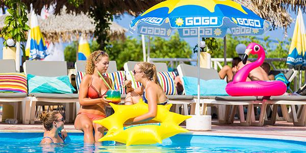 Drie tieners chillen op de rand van het zwembad met een cocktail en opblaasbare zon en flamingo.