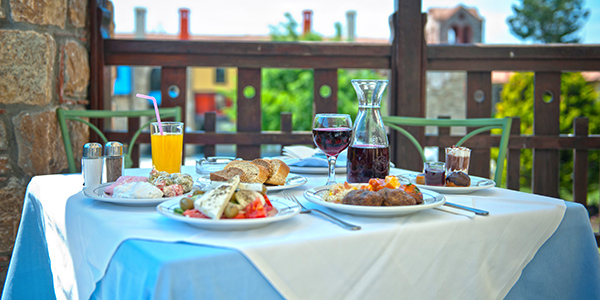 Gedekte tafel met borden met eten, glas wijn en glas met sinaassappelsap.