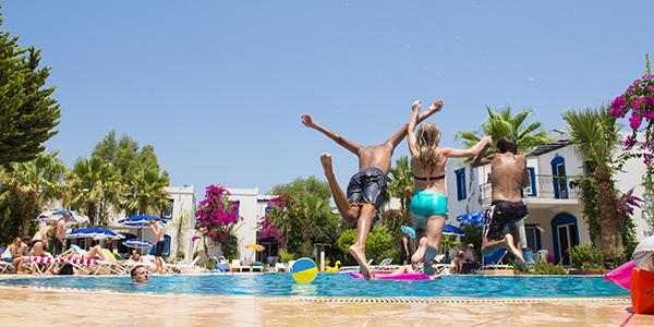 Drie kinderen springen tegelijk in het zwembad bij een hotel.