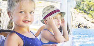Jongetje met hoedje op en meisje met blauw hemd aan op een boot.