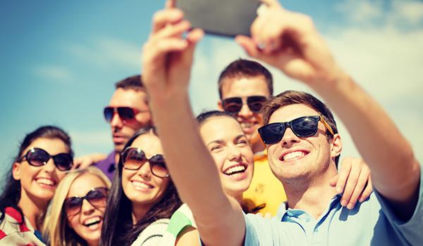 Een groep vrienden met zonnebrillen op neemt een selfie in de zon