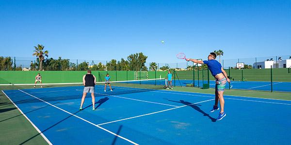 Vier mensen tennissen op een blauwe tennisbaan met helderblauwe lucht.