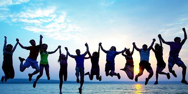 Een groep mensen springt hand in hand in de lucht met de zee en ondergaande zon op de achtergrond