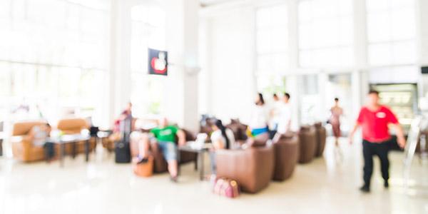 Een drukke lobby van een hotel waar mensen slecht op te zien zijn.