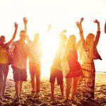 Groep jonge mensen op het strand met armen in de lucht.