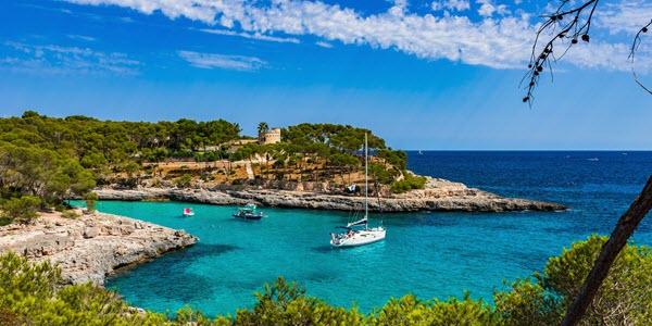 Baai op Mallorca met boten in het helderblauwe water.