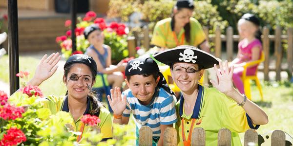 Twee animatoren en een kindje verkleed als piraat zwaaien naar de camera.