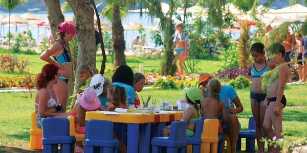 Kinderen spelen buiten aan een gekleurde kindertafel, onder begeleiding van animatoren.