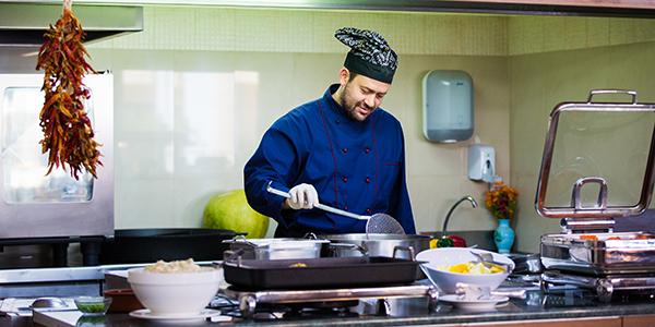 Kok kookt tijdens een all inclusive buffet.
