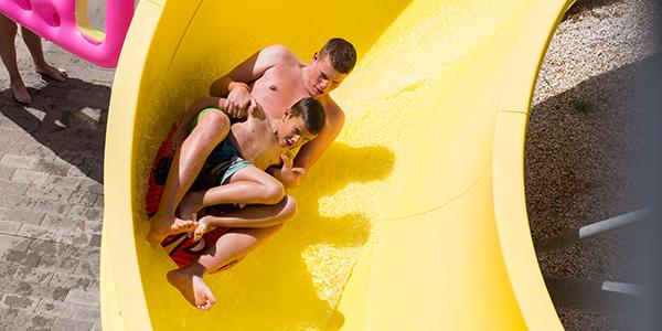 Twee jongens gaan van een gele waterglijbaan.