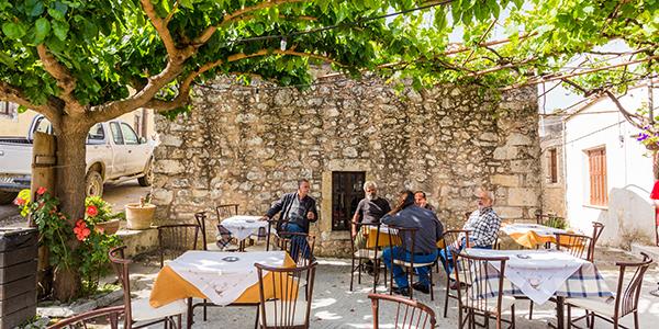 Griekse mannen zitten samen op sfeervol terras onder groene begroeing van bomen