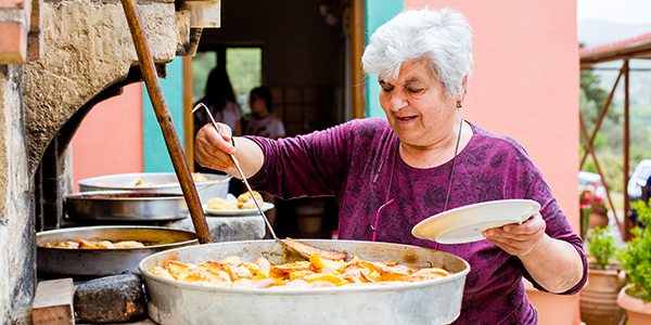 Griekse vrouw kookt grote pan met eten in de buitenlucht