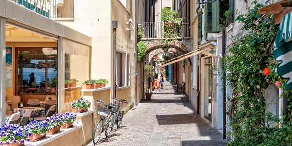 Een zonnig, smal straatje met groene klimop langs de muren.