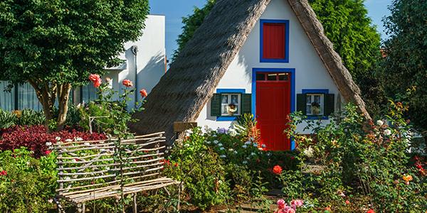 Een wit huisje met een rieten dak, rode deuren en blauwe kozijnen met veel groene begroeiing en bloemen ervoor.