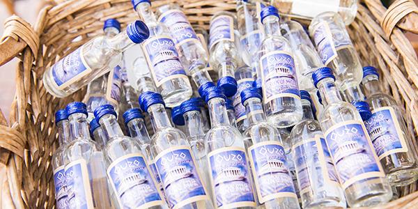 Kleine flesjes ouzo in een mand.