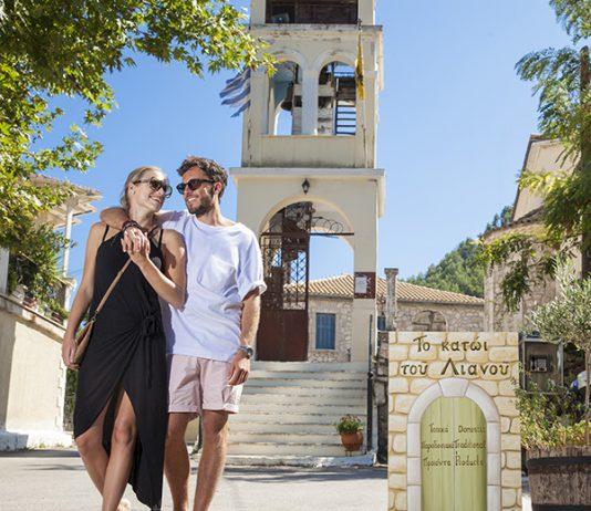 Een koppel loopt over een straat met op de achtergrond een kerkje en een bord met Griekse tekst
