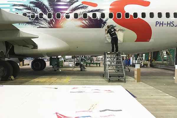 Iemand is het nieuwe Sunweb vliegtuig aan het bestickeren.