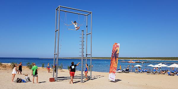 Iemand springt van de trapeze op het strand.