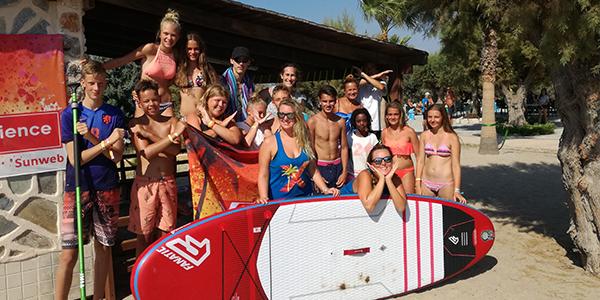 Groep mensen samen met Xperience Holiday Makers en een surfboard.