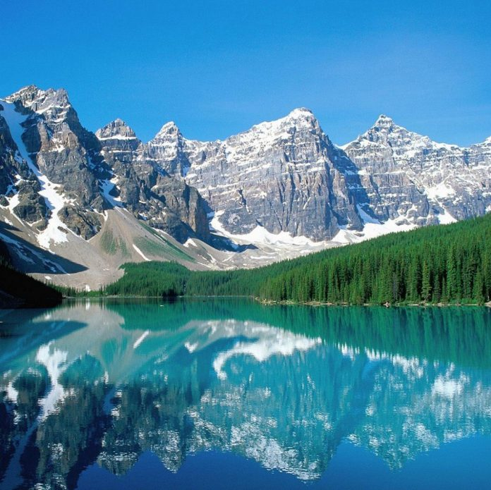 Lac entouré de montagnes au sommets enneigés.